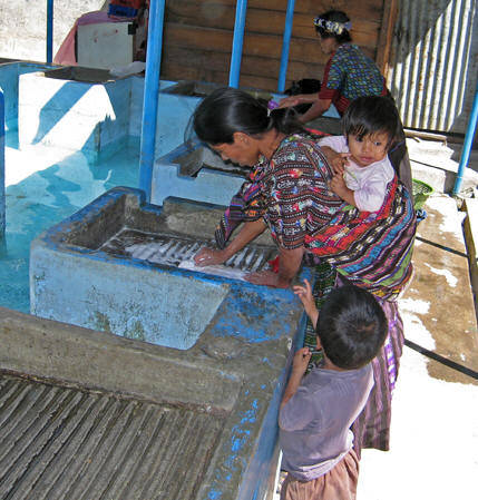 "It's laundry day and the Maya women are doing their wash at the new ""laundromat"" in town. Water has been diverted from a mountain stream and made available in the central area for women to gather and clean clothes. Lago Atitlan, Guatemala."