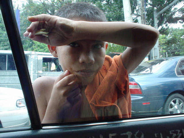 Boy in Philippines Begging at Taxi Window