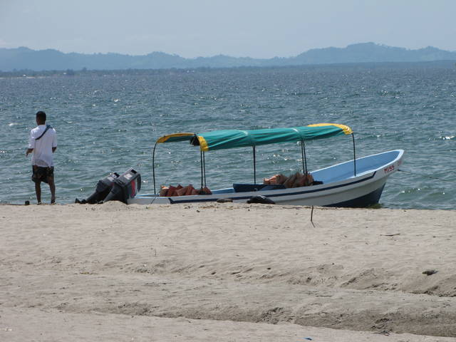 Right on a simple island there is a boat waiting for passengers.