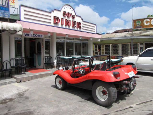 Dune Buggy parked right in front of a restaurant.