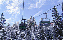 Moving snowy chairlift brings vacationers to their destination.